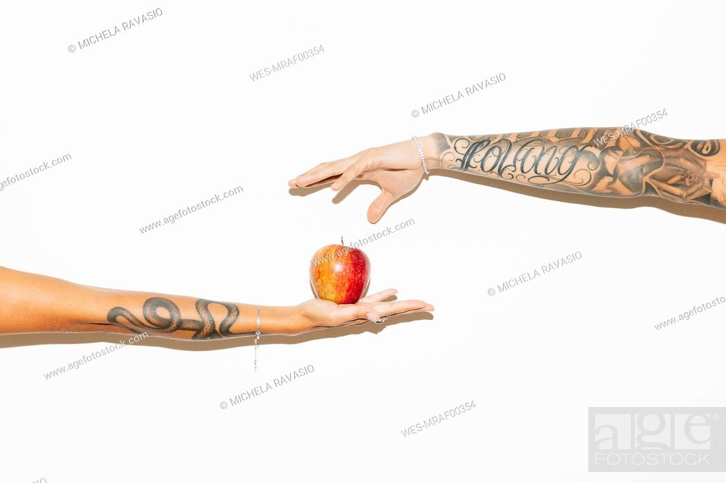 Stock Photo: Woman's hand offering an apple to a man.