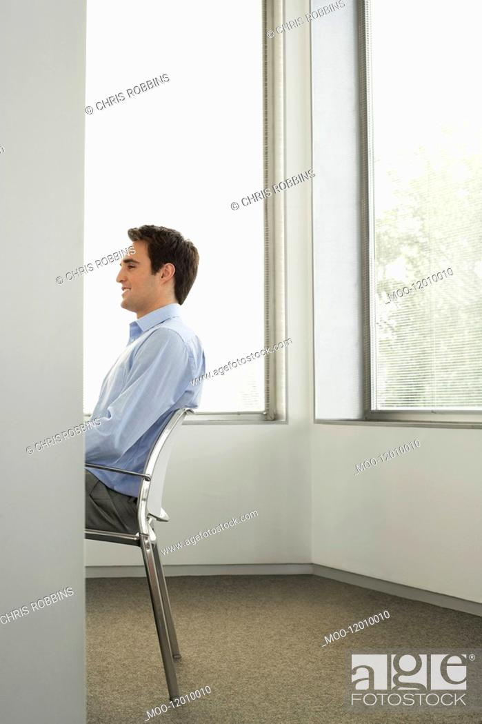 Stock Photo: Businessman sitting on chair in office side view half length.