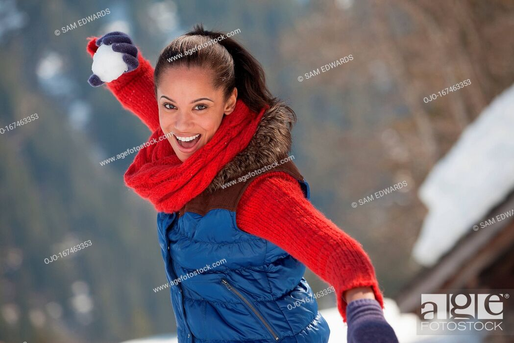 Stock Photo: Portrait of smiling woman throwing snowball.