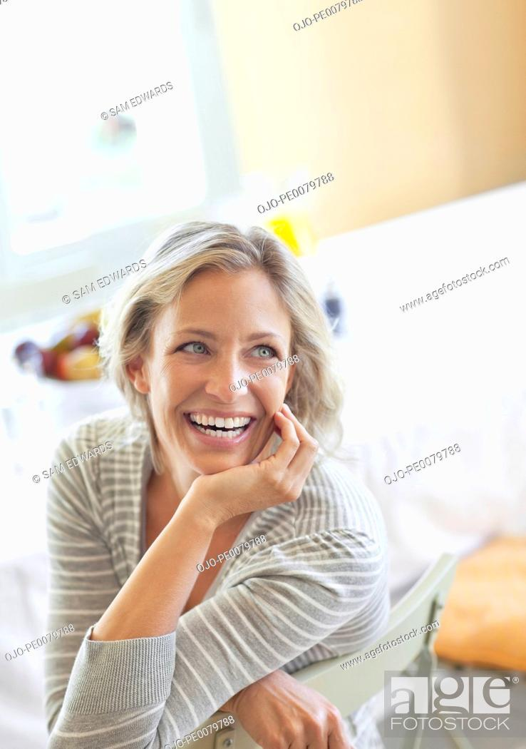 Stock Photo: Happy woman with hand on chin.