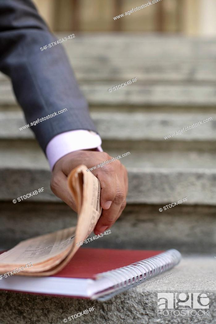 Stock Photo: Hand taking a newspaper.