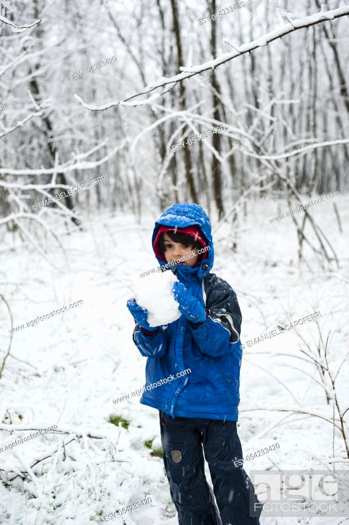 Stock Photo: Child plays with snow under a heavy snowfall.