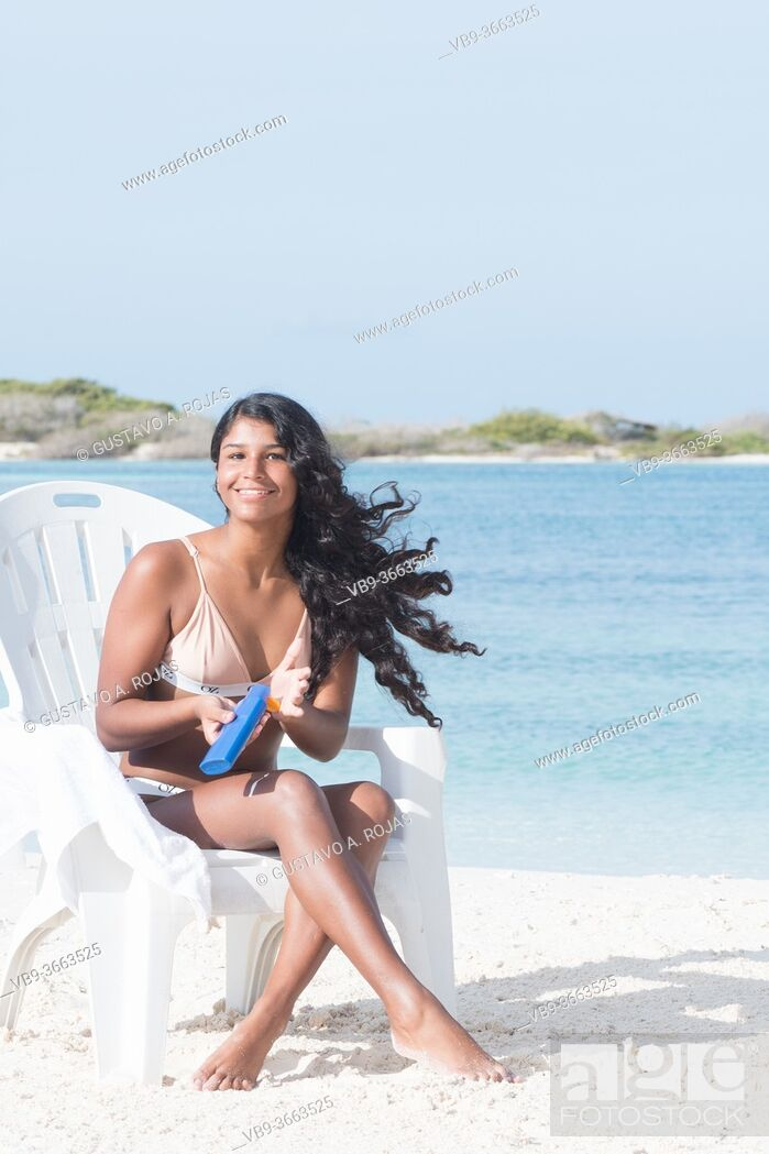 Stock Photo: Happy Young Woman enjoing summer applying SPF Sunscreen lotion at Tropical Beach on the beach chair.