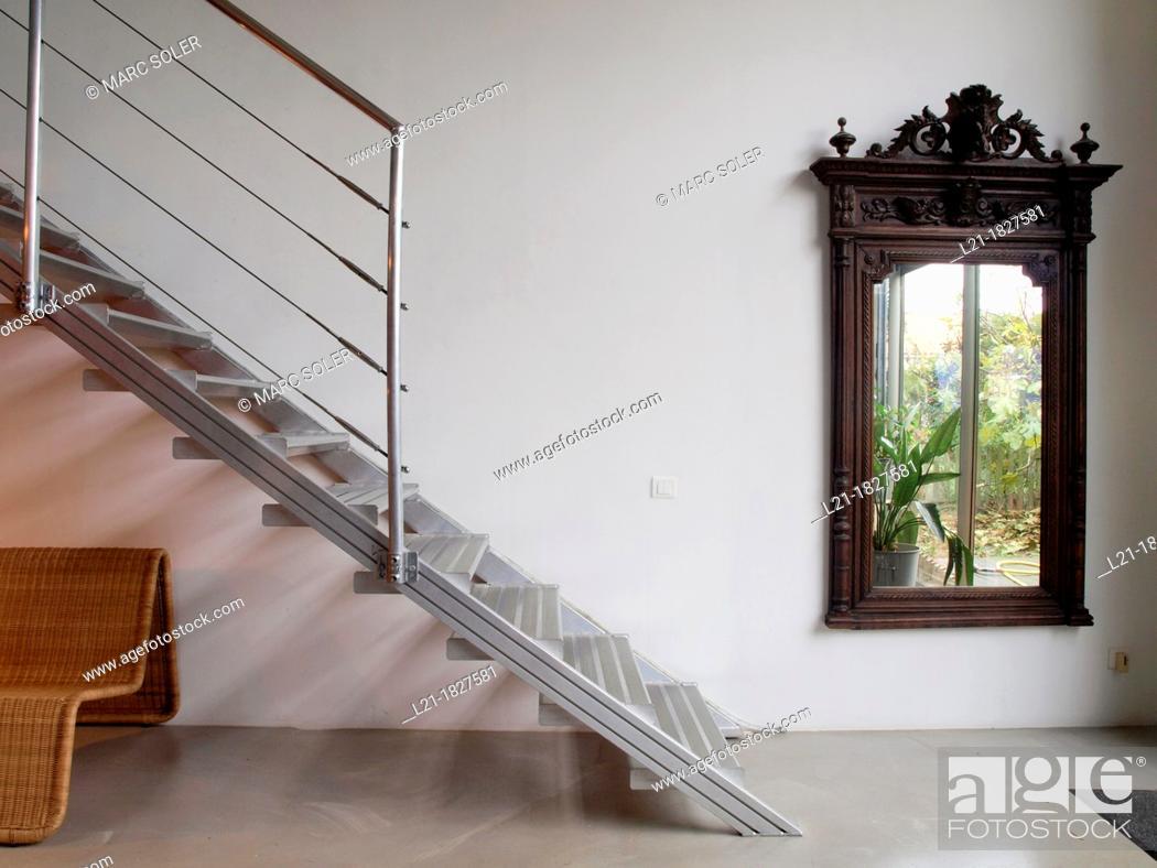 Stock Photo: Big wooden mirror. Metallic staircase. Cane armchair. Interior designed by Gabriel Rodriguez.