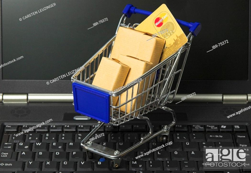 Stock Photo: Online shopping, a shopping cart filled with parcel and a credit card standing on the keyboard of a notebook computer.