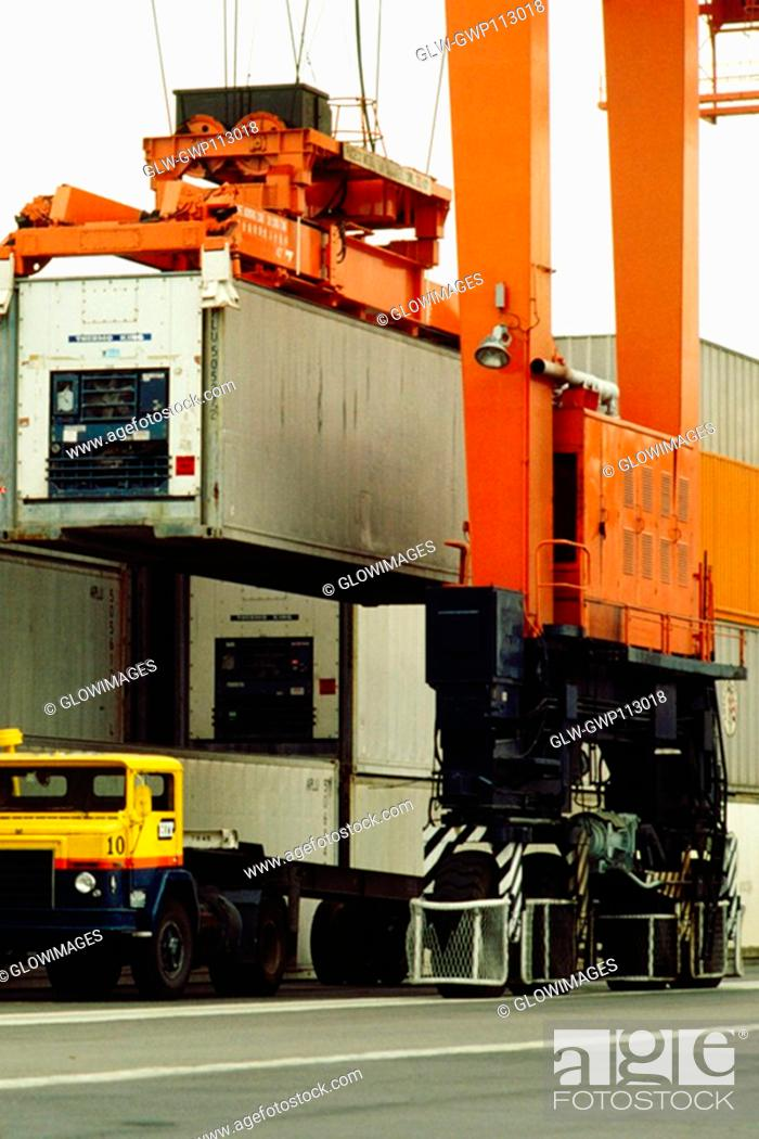 Stock Photo: Container being loaded on a ship by a crane, Hong Kong, China.