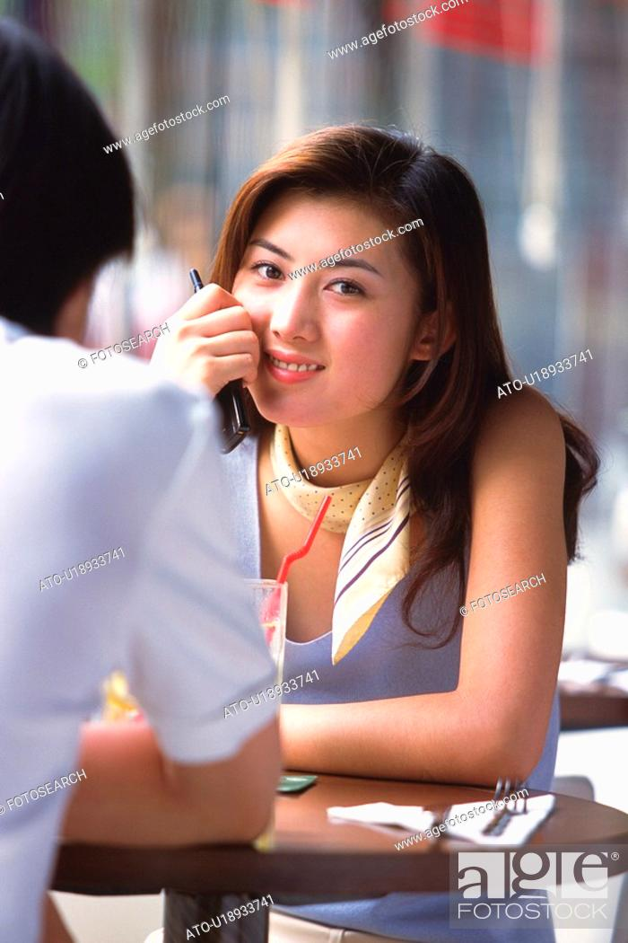 Imagen: Image of a Young Adult Woman Having a Drink With a Man, Looking at Camera, Smiling, Front View, Rear View, Differential Focus.