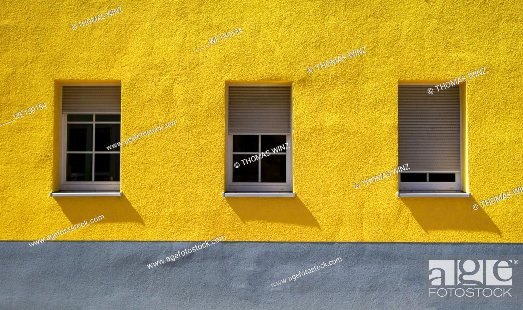 Stock Photo: Yellow wall with three windows and shutters in different positions , Baden Württemberg, Germany.