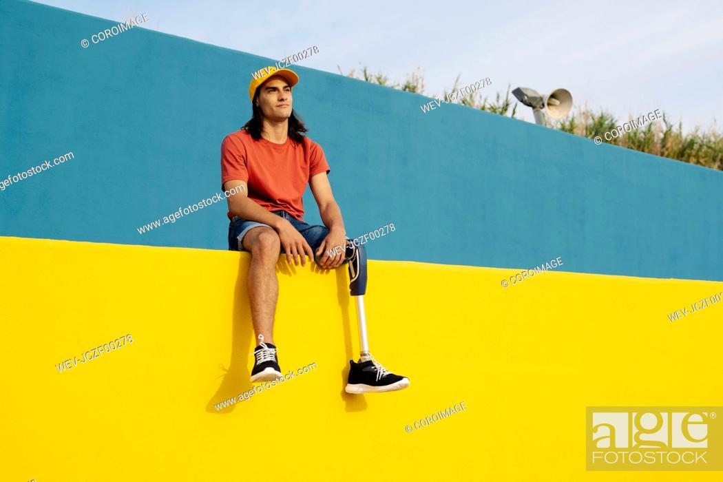 Stock Photo: Disabled man wearing cap sitting on multi colored wall.