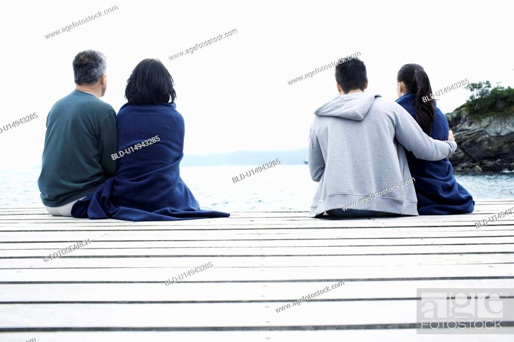 Stock Photo: Mature and young couple on jetty.