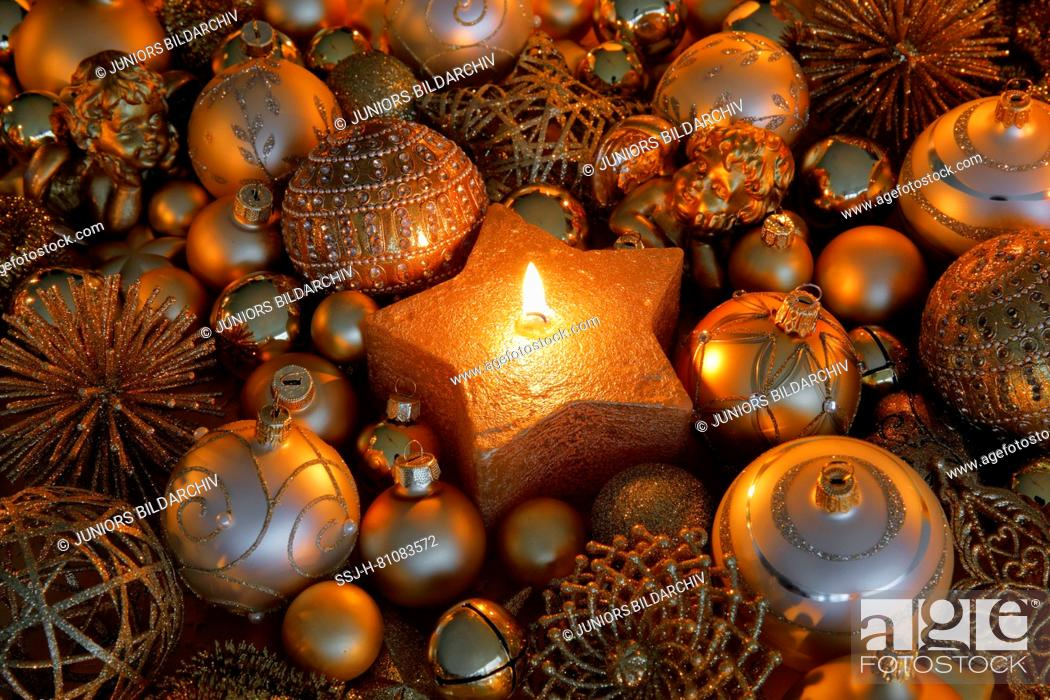Stock Photo: Golden Christmas baubles and burning tealight in a star-shaped candle holder. Studio picture. Switzerland.