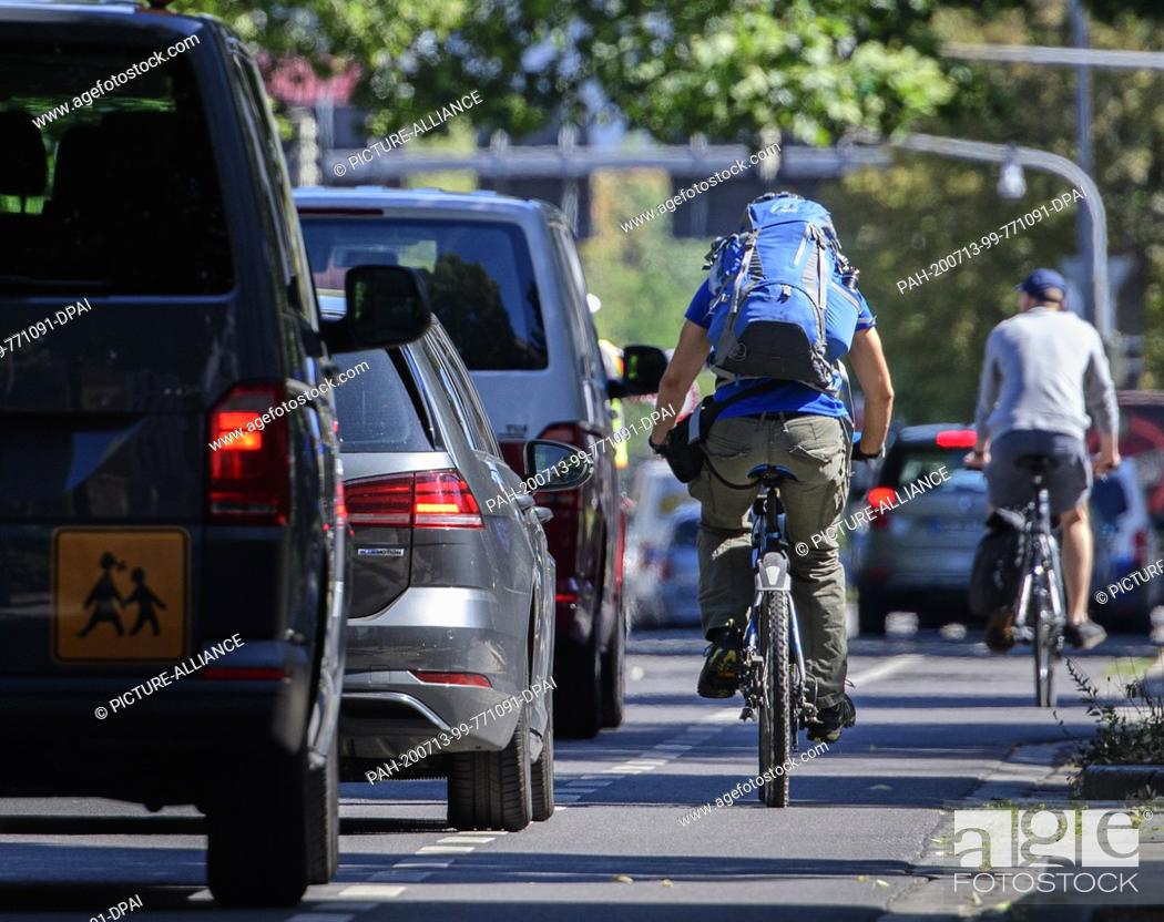 Stock Photo: 13 July 2020, Saxony, Dresden: Cars overtake cyclists on a street in the city centre. During a police control, the observance of the minimum distance of 1.