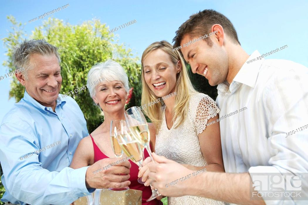 Stock Photo: Young couple and older couple Toasting with Champagne outside.