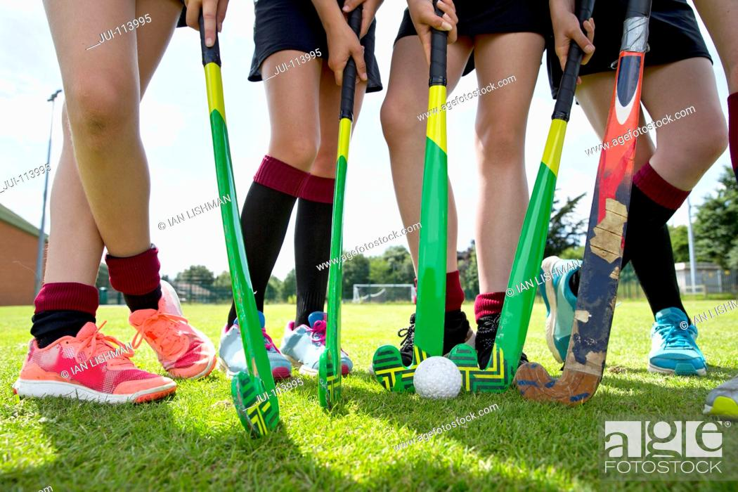 Stock Photo: Legs of middle schoolgirls playing field hockey in physical education class.