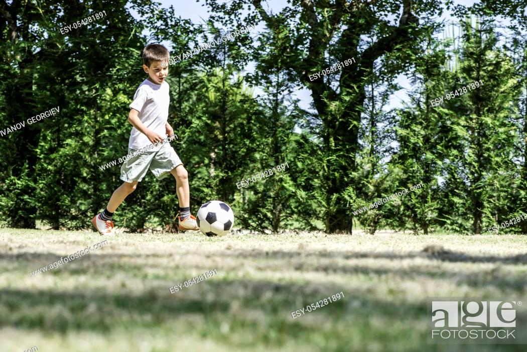 Stock Photo: Child playing football in a stadium. Trees on the background.