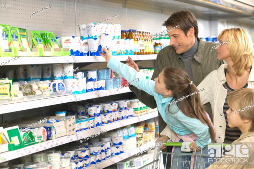 Stock Photo: Family shopping in supermarket, girl (8-10) reaching for product on shelf.