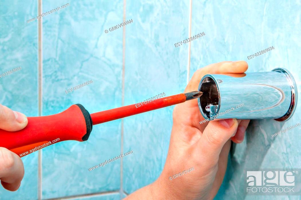 Stock Photo: Residential plumbing repair, closeup hands plumber with screwdriver, install wall mounted height adjustable shower bar slide rail bracket.