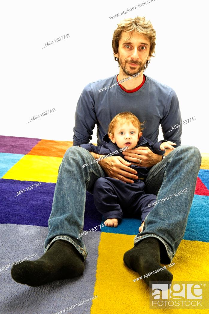 Stock Photo: Father hold his 10 months old baby while on a multi coloured carpet.