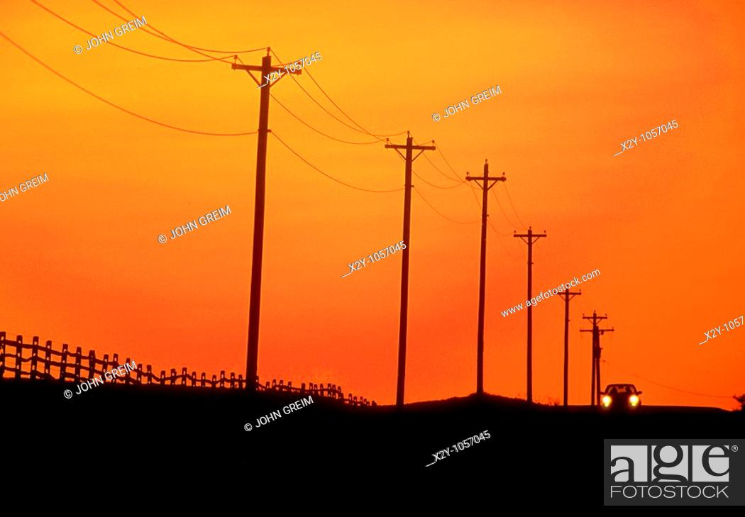 Stock Photo: The distant headlights of a lone aproaching car as it travels over a country road, past an expanse of telephone lines and poles in silhouette under a sunset sky.