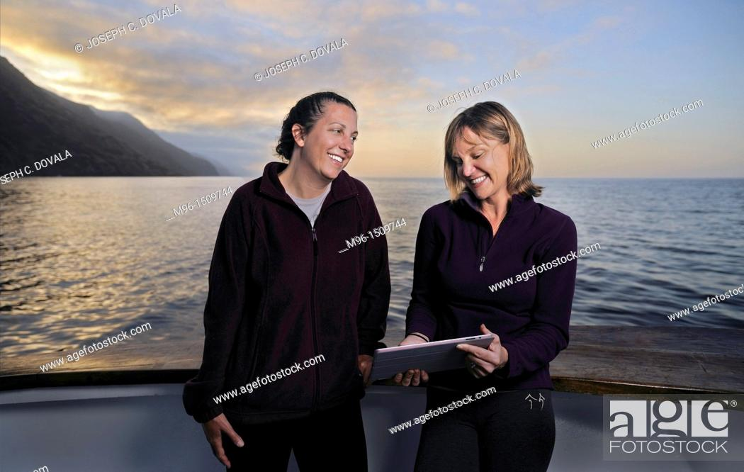 Stock Photo: Pair of female divers looking at tablet after a day of diving, San Clemente Island, California, USA.