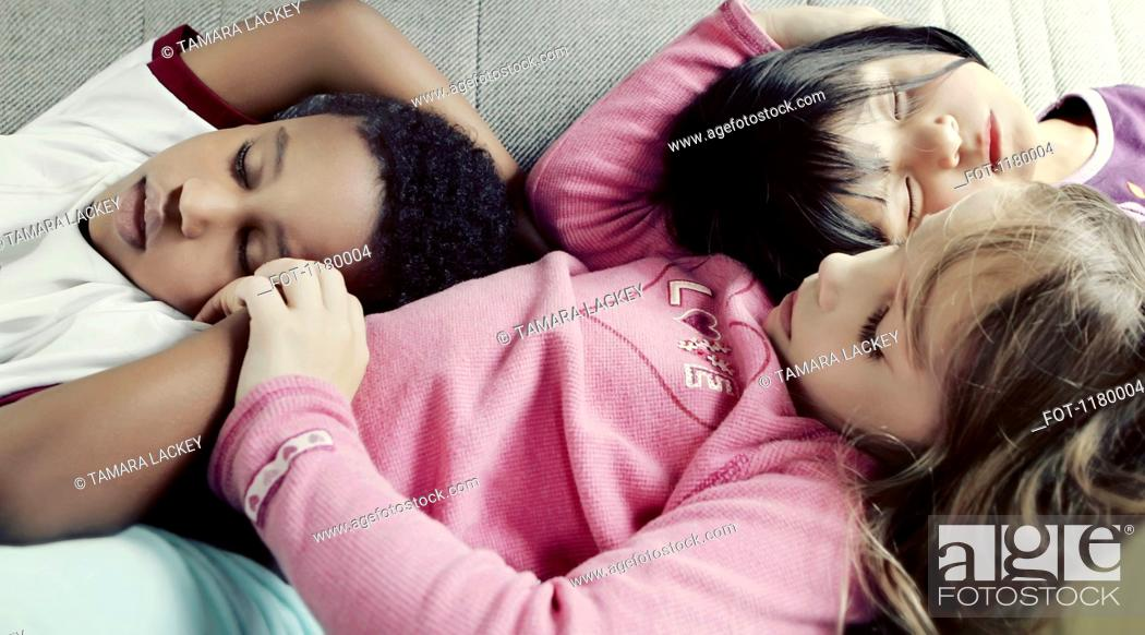 Stock Photo: Three kids comfortably napping together on a sofa.