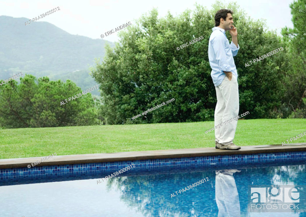 Stock Photo: Man using cell phone by edge of pool.