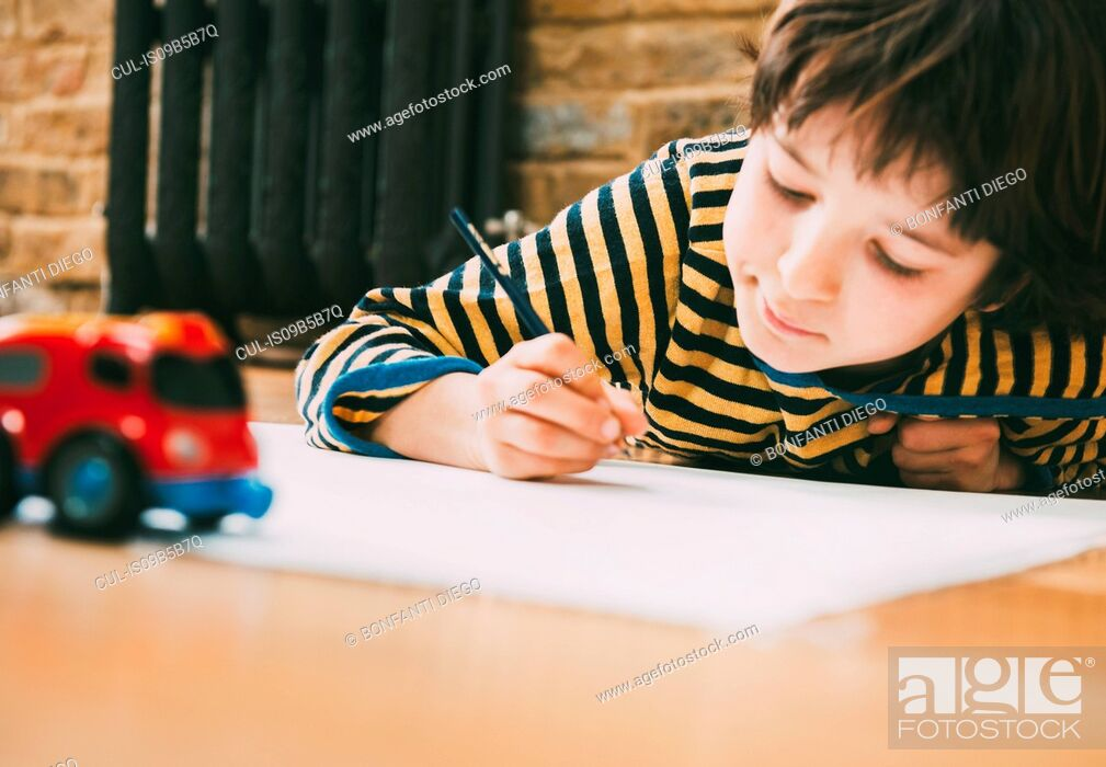 Imagen: Boy lying on floor drawing on paper.