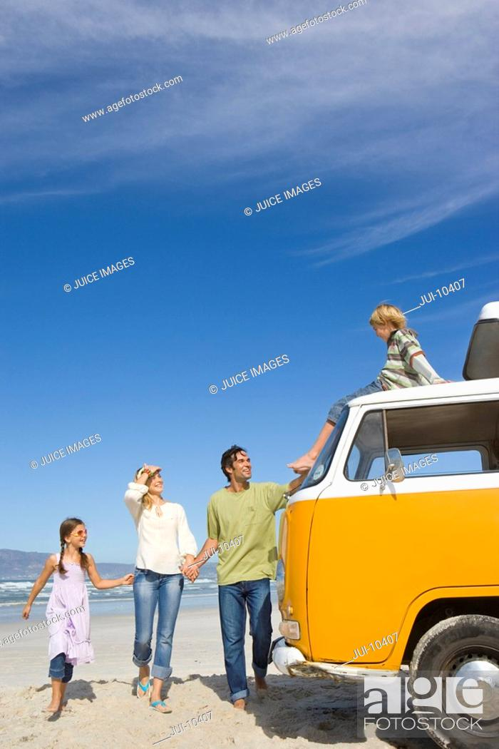 Stock Photo: Family of four on beach looking at son 6-8 on roof of camper van.