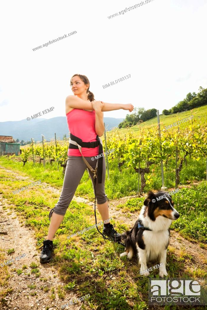Stock Photo: Caucasian woman with dog stretching in vineyard.