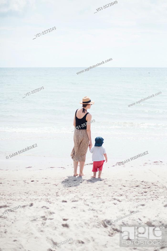 Stock Photo: 2 years old boy with his mother at the beach.