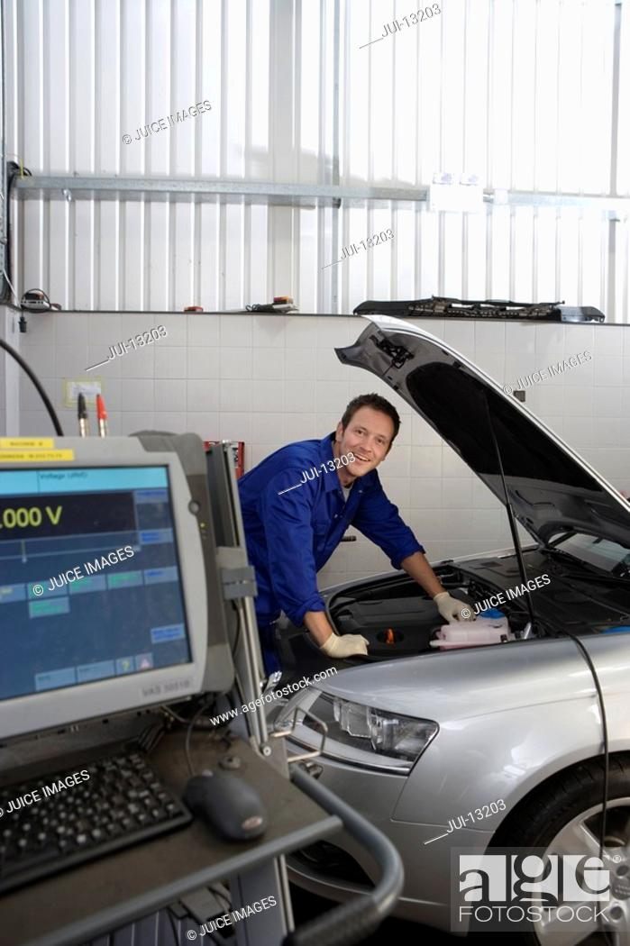 Stock Photo: Mechanic working on car by computer, smiling, portrait.