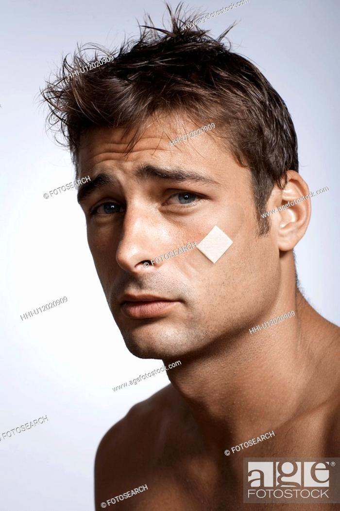 Stock Photo: Mid adult man with adhesive plaster on cheek.