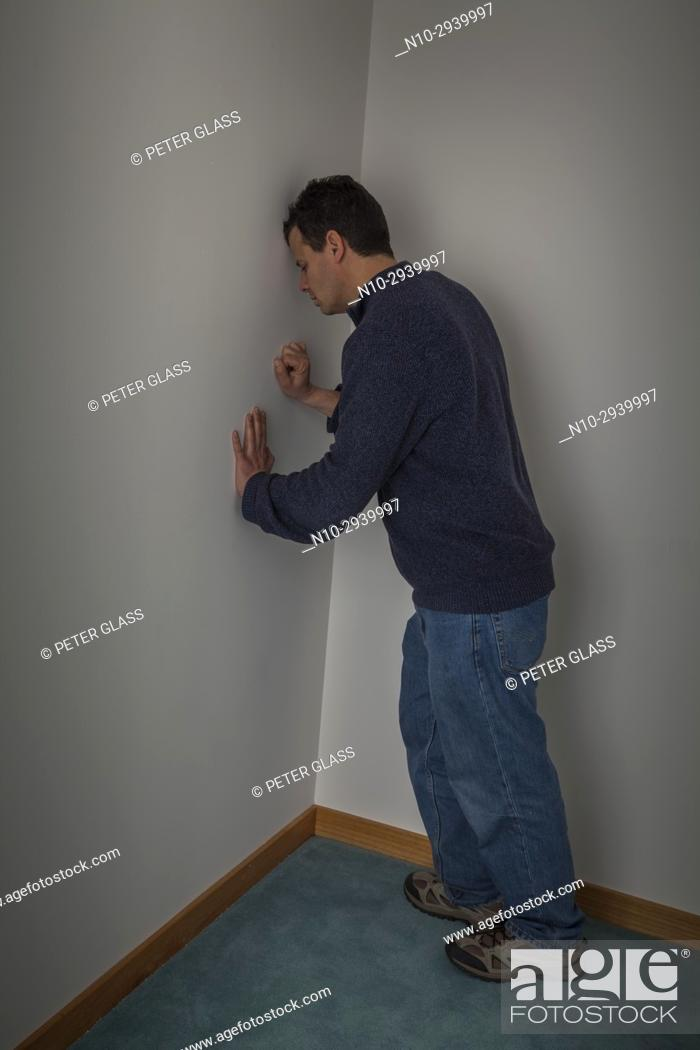 Stock Photo: Middle age man leaning against wall in the corner of a room.