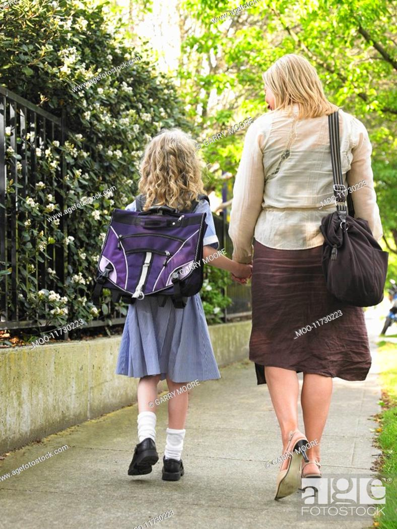 Stock Photo: Elementary schoolgirl walking with mother on pavement back view.