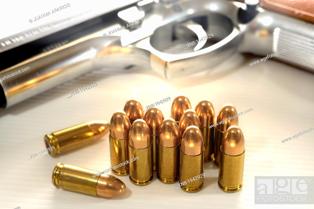 Imagen: 9mm bullets and gun at background.