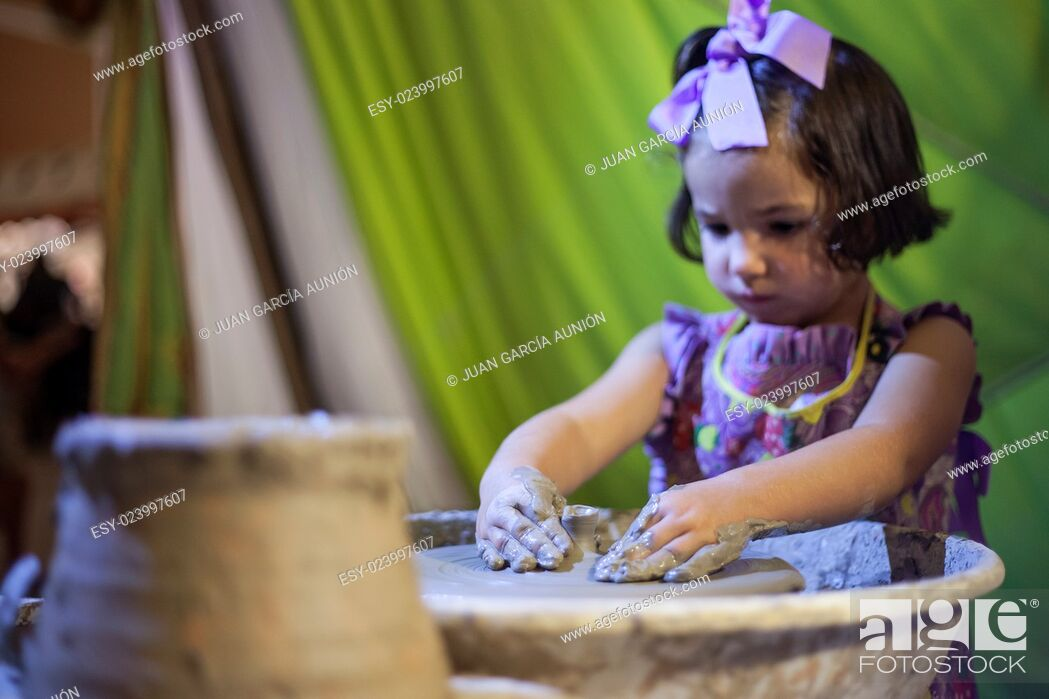 Imagen: Little girl learning to work with potter's wheel. Selective focus.