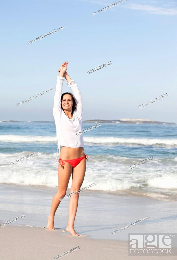 Stock Photo: Teenager stretching and walking on beach.