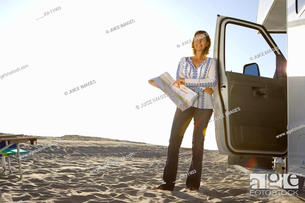 Stock Photo: Mature woman with map by motor home on beach, smiling, low angle view lens flare.
