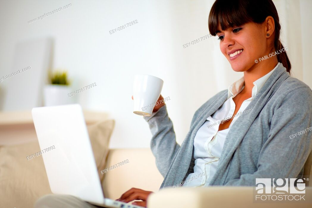 Stock Photo: Portrait of a smiling young woman with a mug sitting on sofa browsing the internet on her laptop at home indoor.