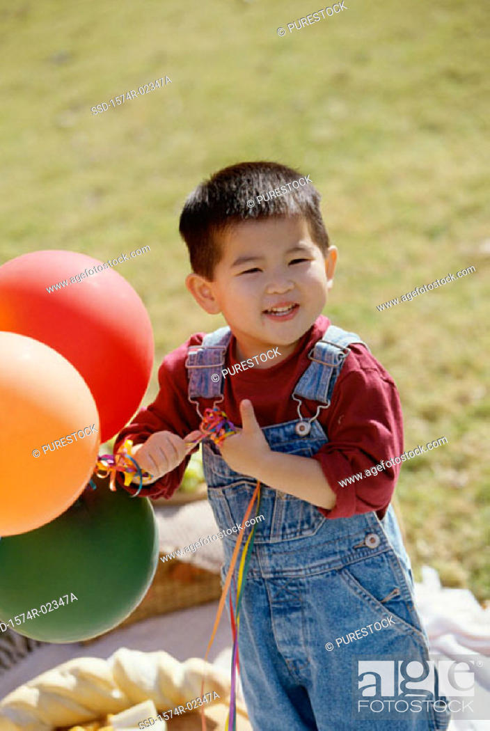 Stock Photo: Portrait of a boy holding balloons.
