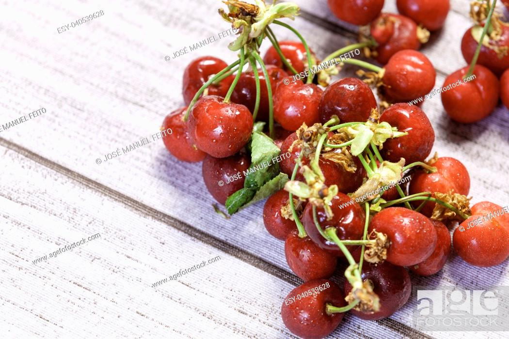 Stock Photo: heap fresh cherries on wood.