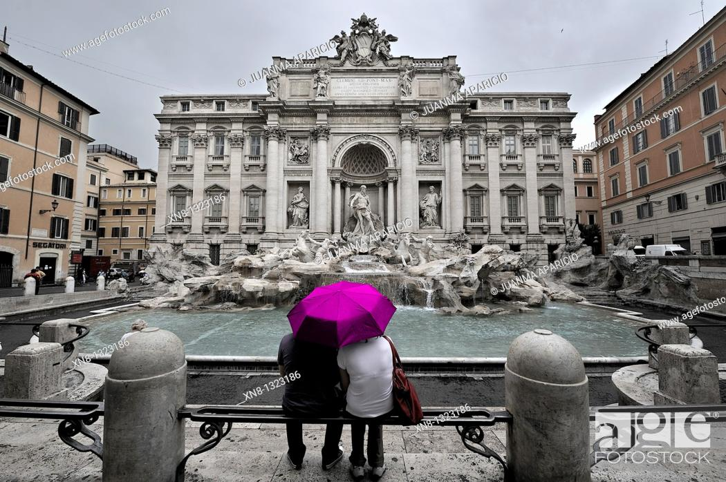 Imagen: Image with low color saturation of a couple sitting in front of the Trevi Fountain on a hot pink umbrella on a rainy day.