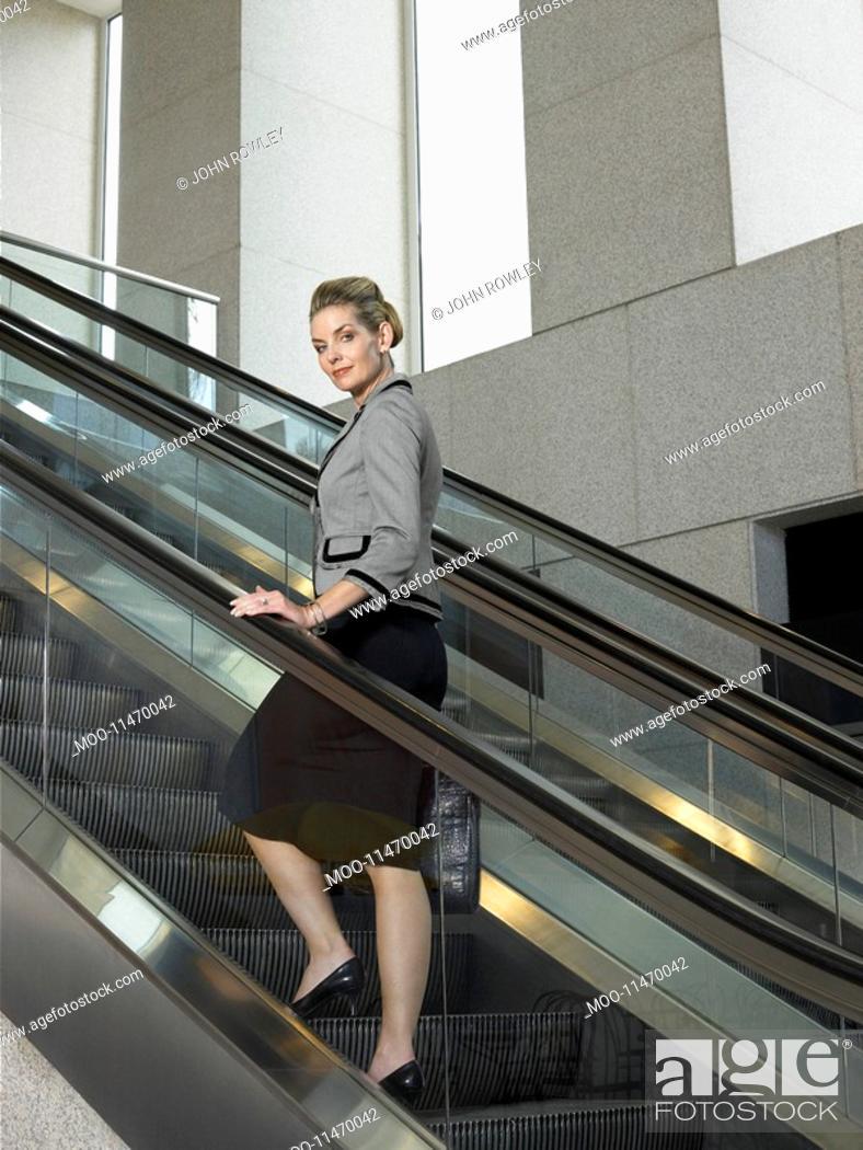 Stock Photo: Businesswoman on escalator portrait.
