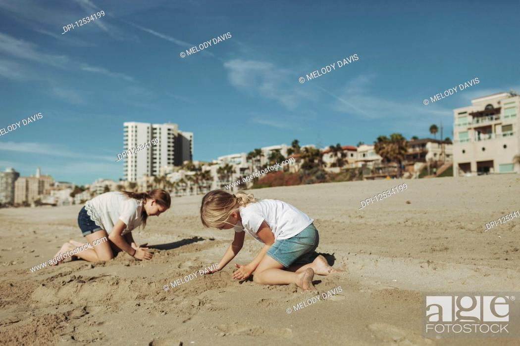 Imagen: Two girls playing in the sand at the beach with condominium buildings in the background; Long Beach, California, United States of America.