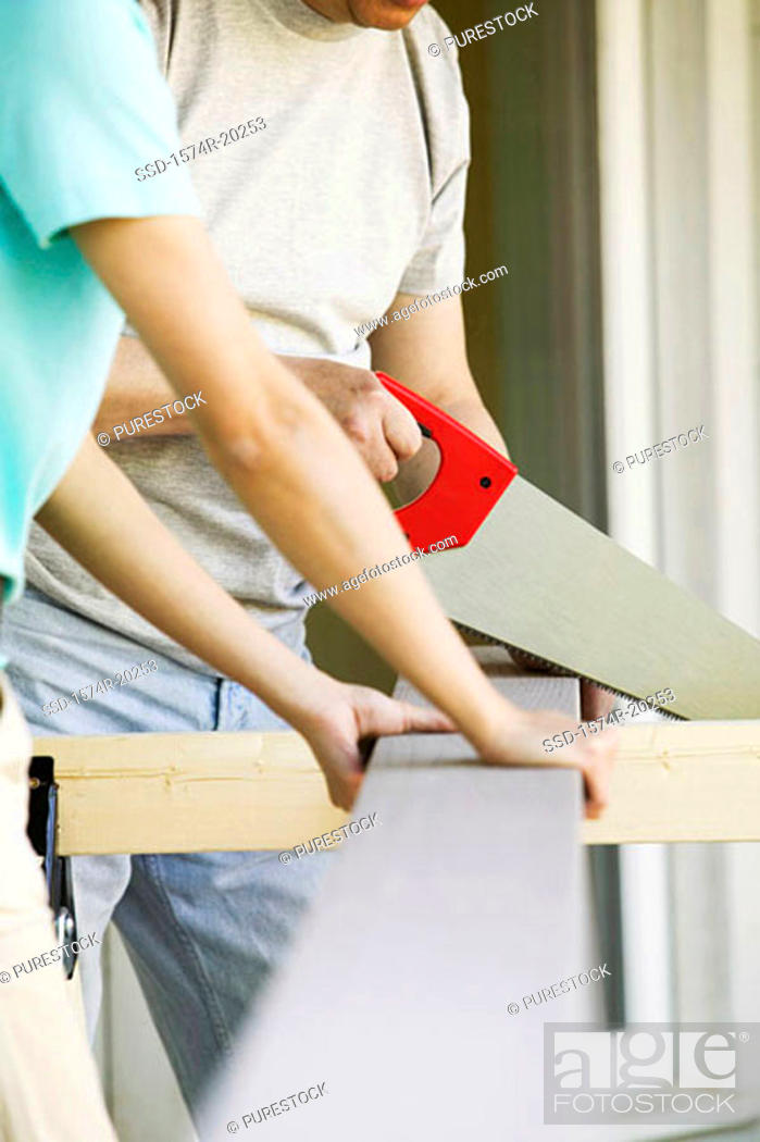 Stock Photo: Close-up of a woman standing with a man cutting a plank with a saw.