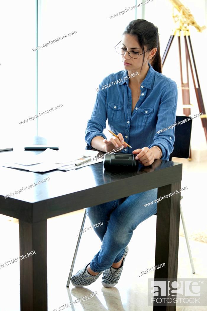 Stock Photo: Woman using calculator at desk.