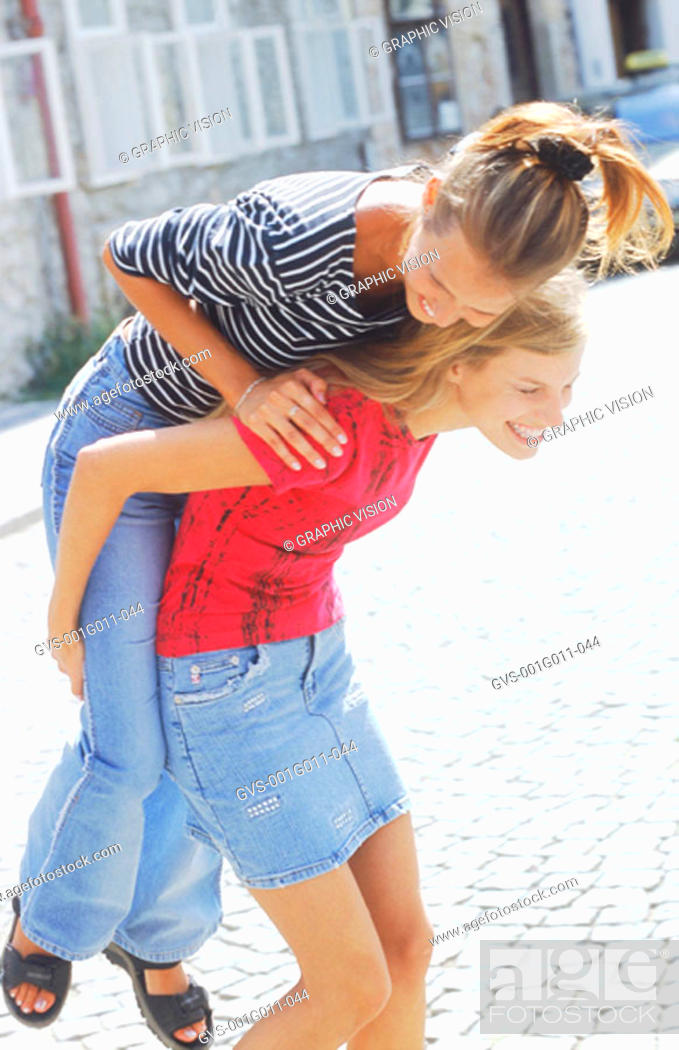 Stock Photo: Two young women riding piggyback.