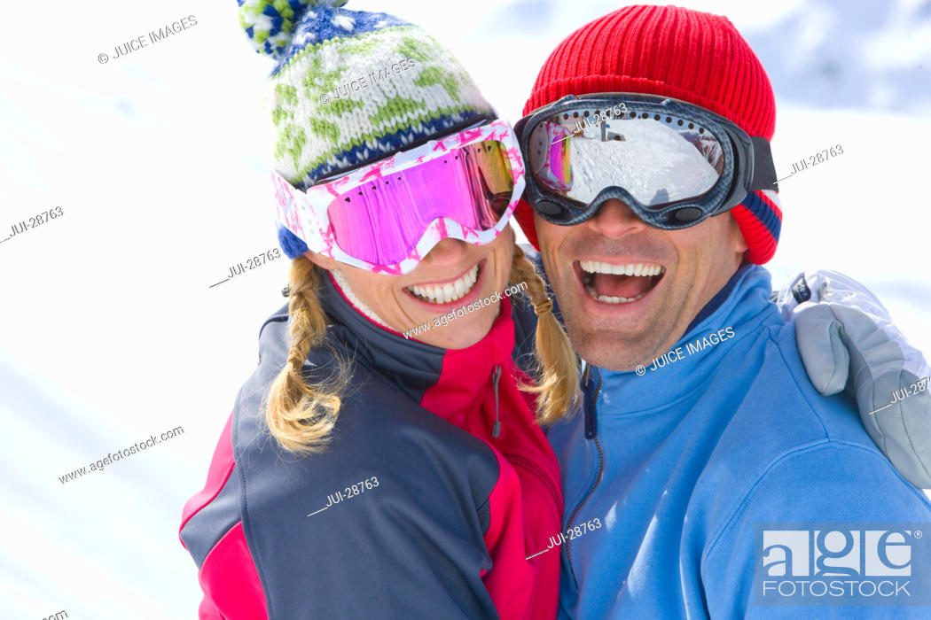 Stock Photo: Smiling couple wearing goggles, hugging.