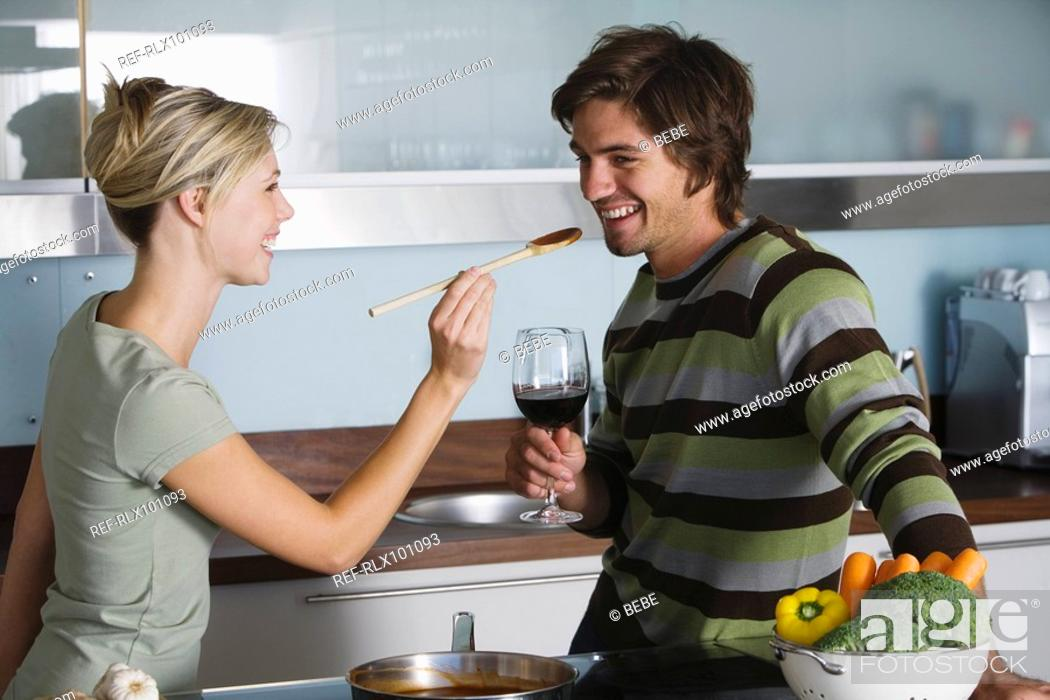 Stock Photo: Young couple in modern kitchen, cooking, drinking red wine, tasting food.