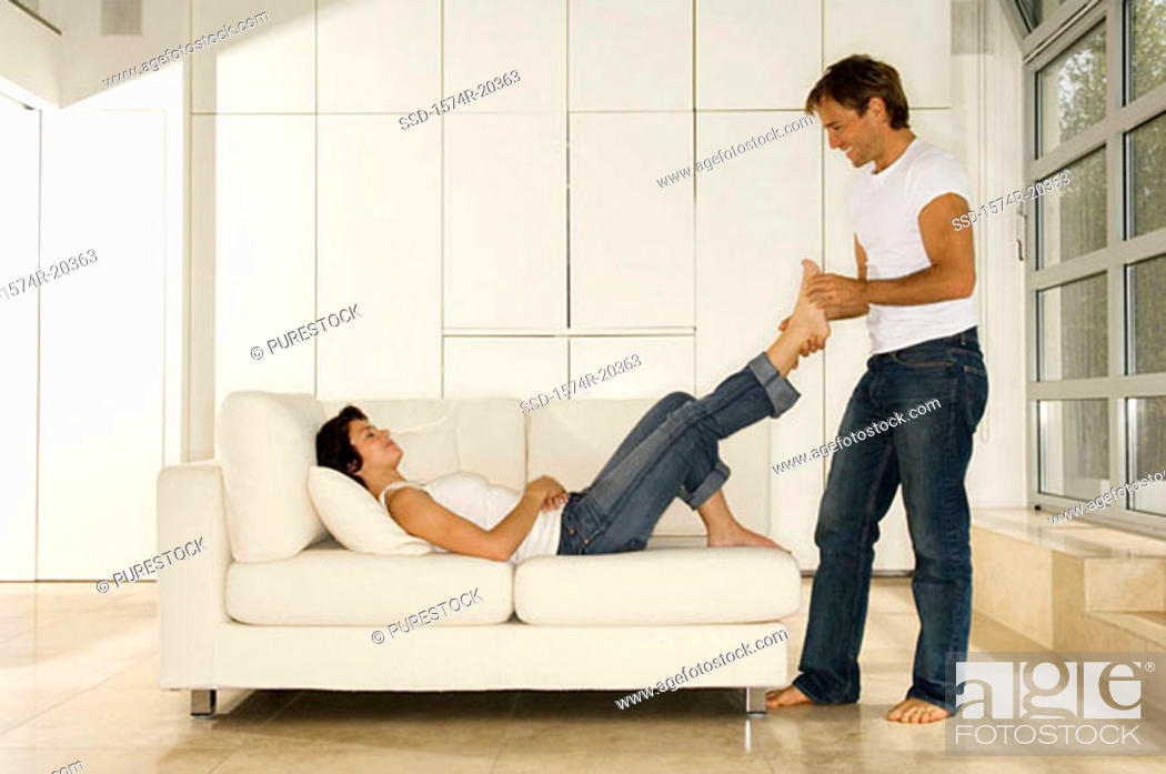 Stock Photo: Side profile of a young man holding the foot of a young woman.